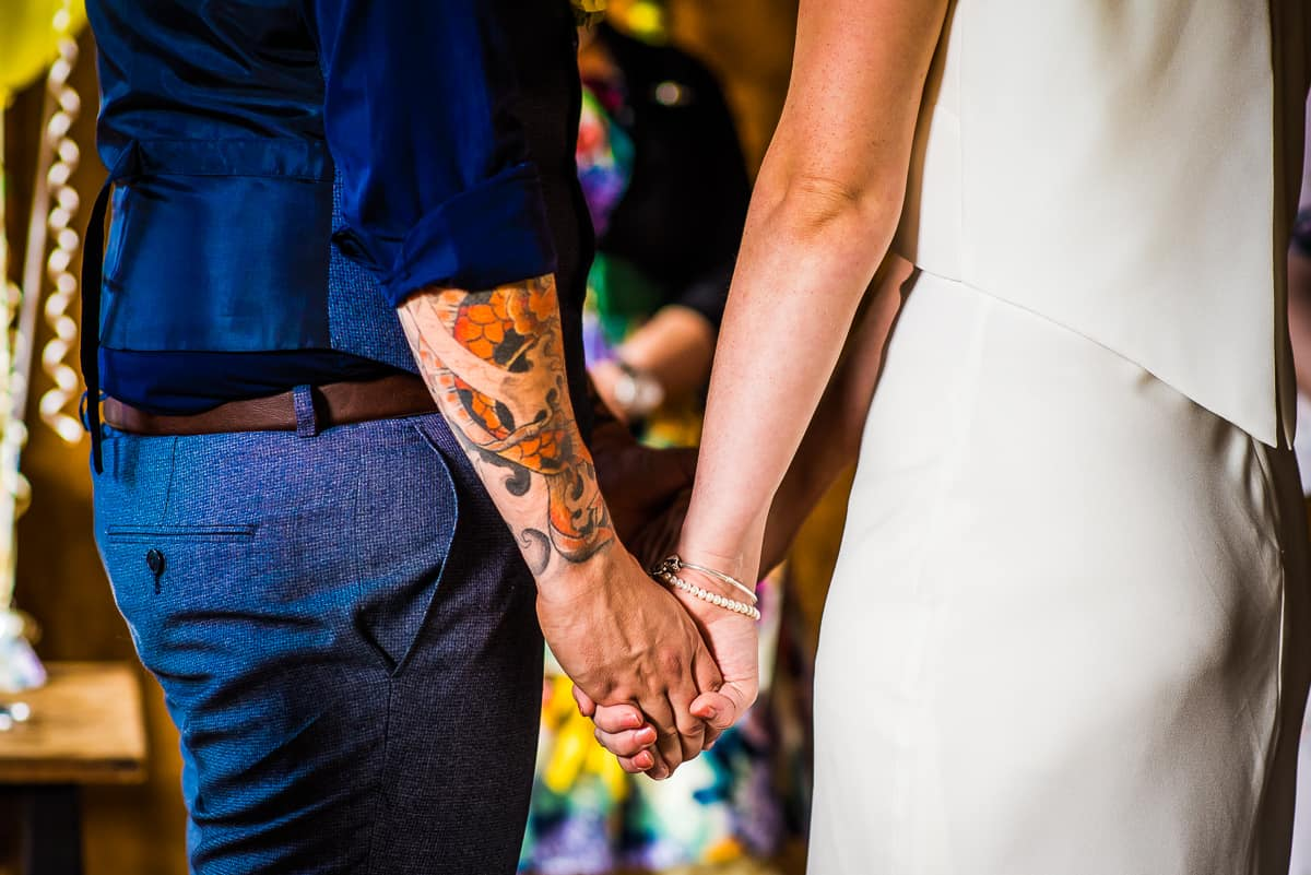 Bride and Groom holding hands during their small wedding service