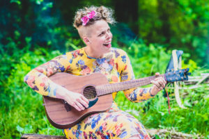 Female guitarist sings around a campfire at a wedding in the New Forest