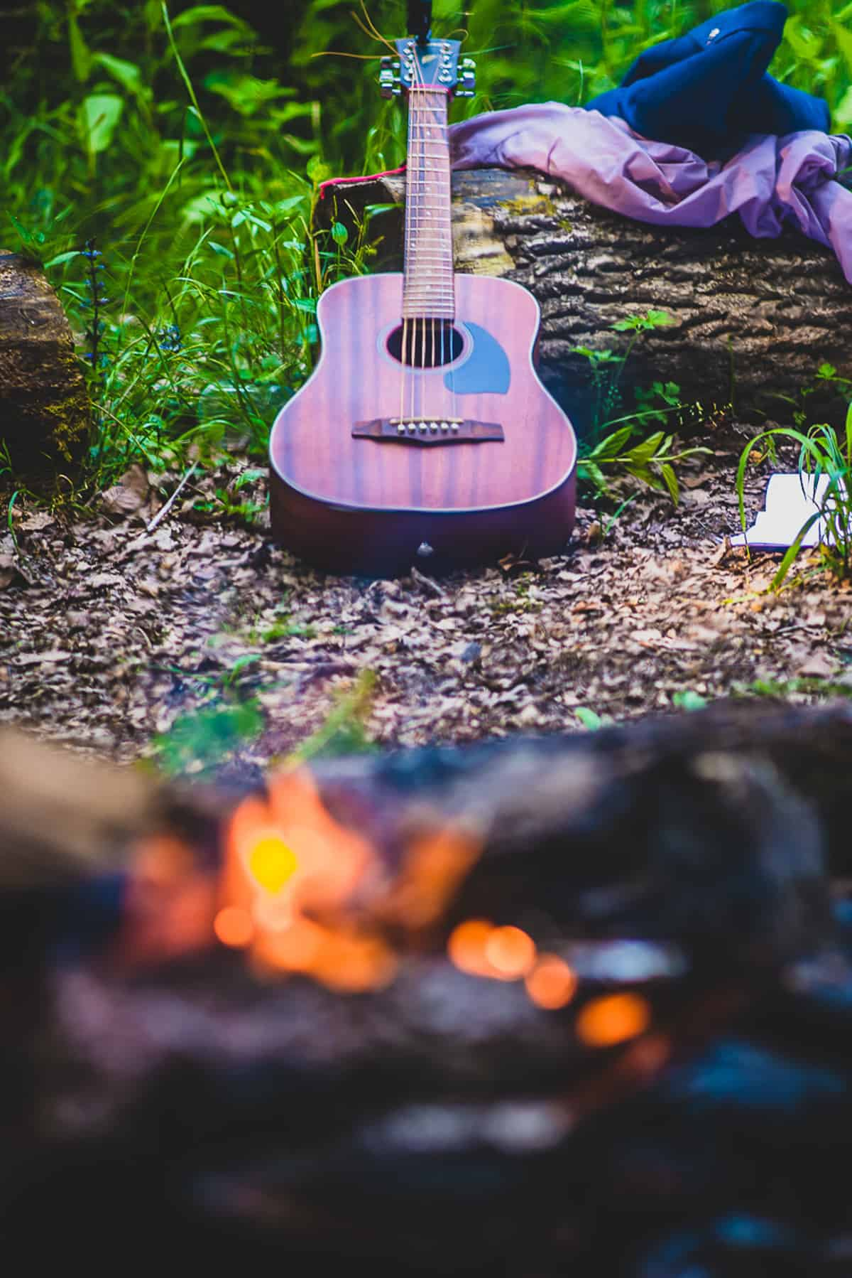 An acoustic guitar and campfire