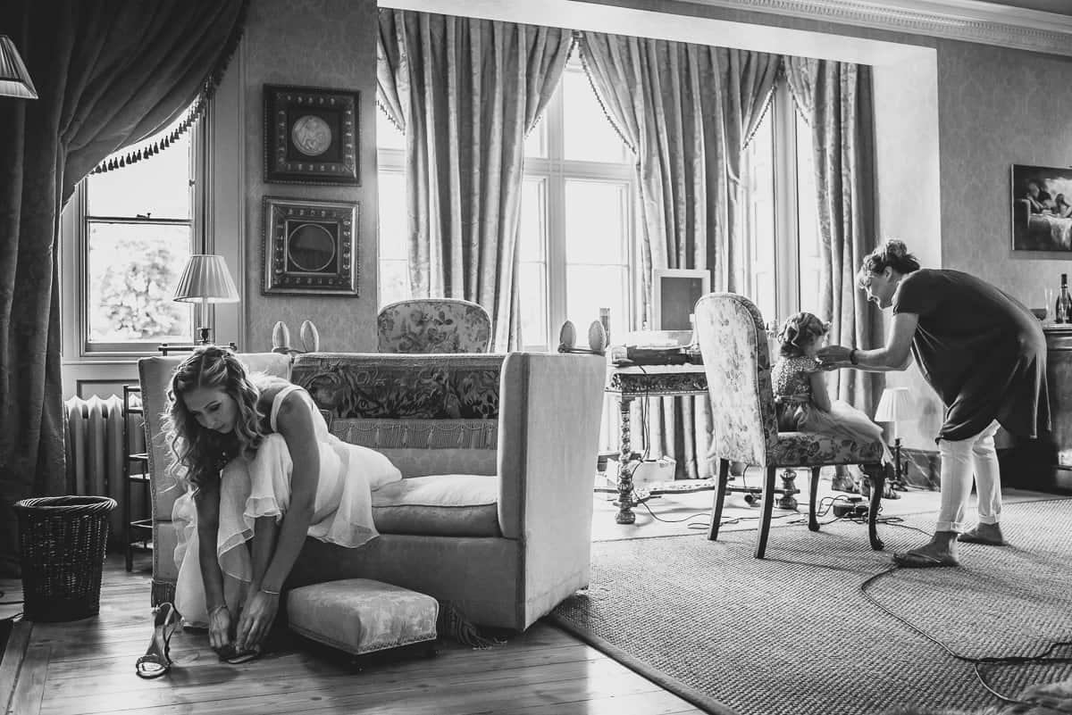 Bride puts on her shoes before her relaxed and informal wedding at Ladyham Hall.