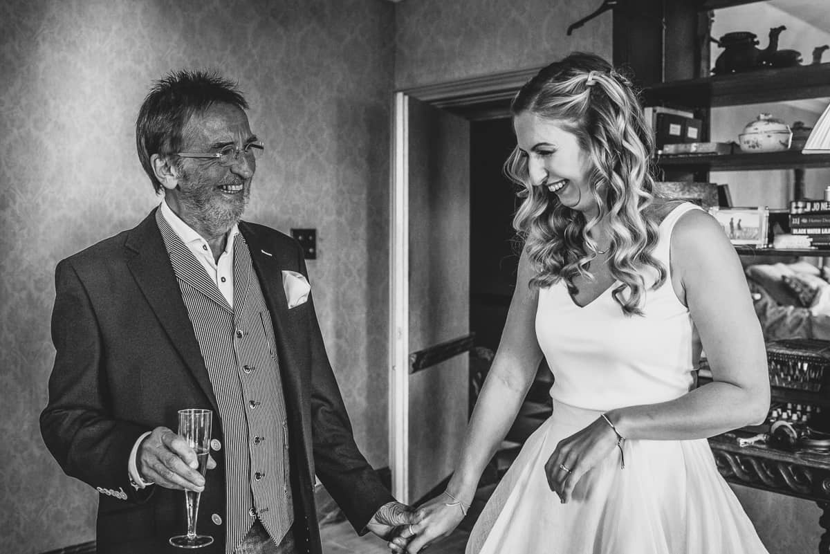 Black and white image of a smiling bride holding her Dad's hand.