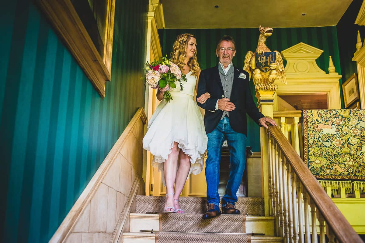 Bride and her Dad walk down the stairs before her informal wedding ceremony at Ladyham Hall in Northamptonshire.