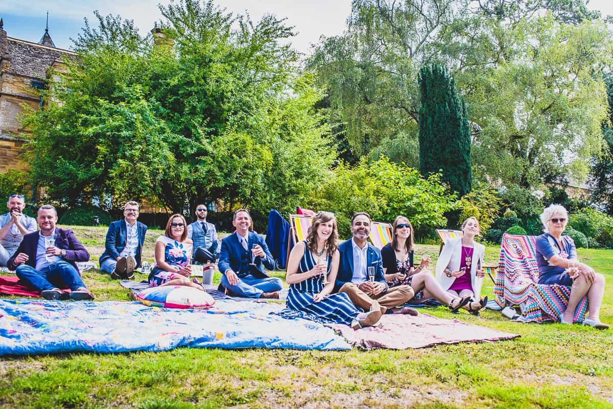 Guesst sit on blankets at ceremony of super relaxed and informal wedding.
