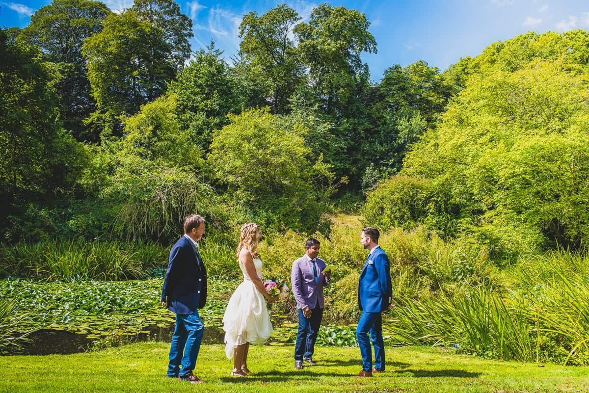 A Friend conducts a formal exchanging of vows and informal wedding ceremony by the lake.