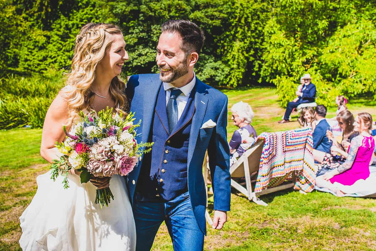Couple walk an imaginary aisle at fun, informal and non-tradition humanist wedding.