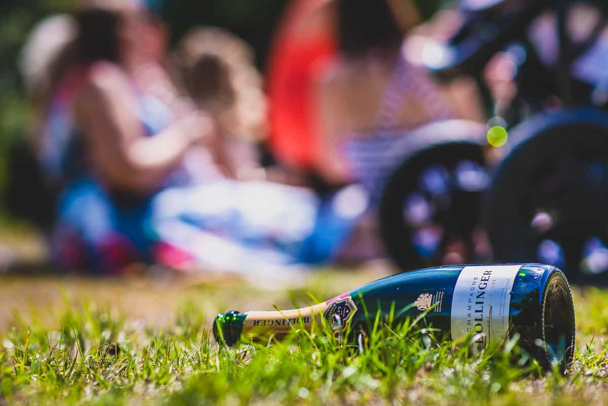 An empty bottle go Bollinger champagne rests on the grass.