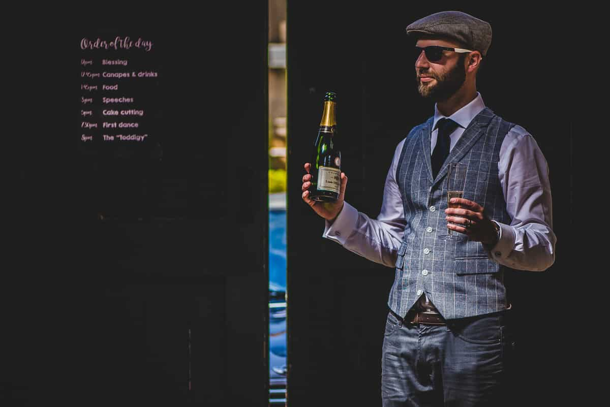 Wedding guest holding a glass and bottle of bolo linger champagne.