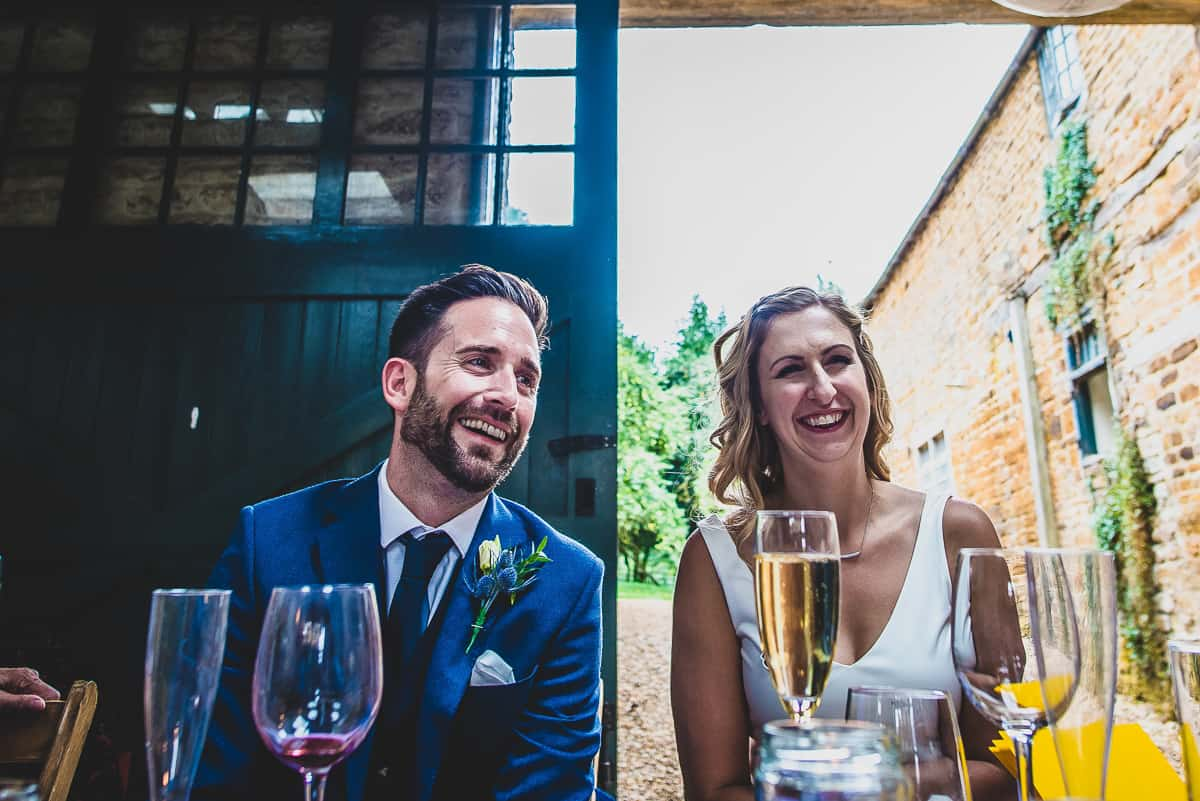 Bride and Groom laughing during the speeches of their very relaxed and informal wedding.
