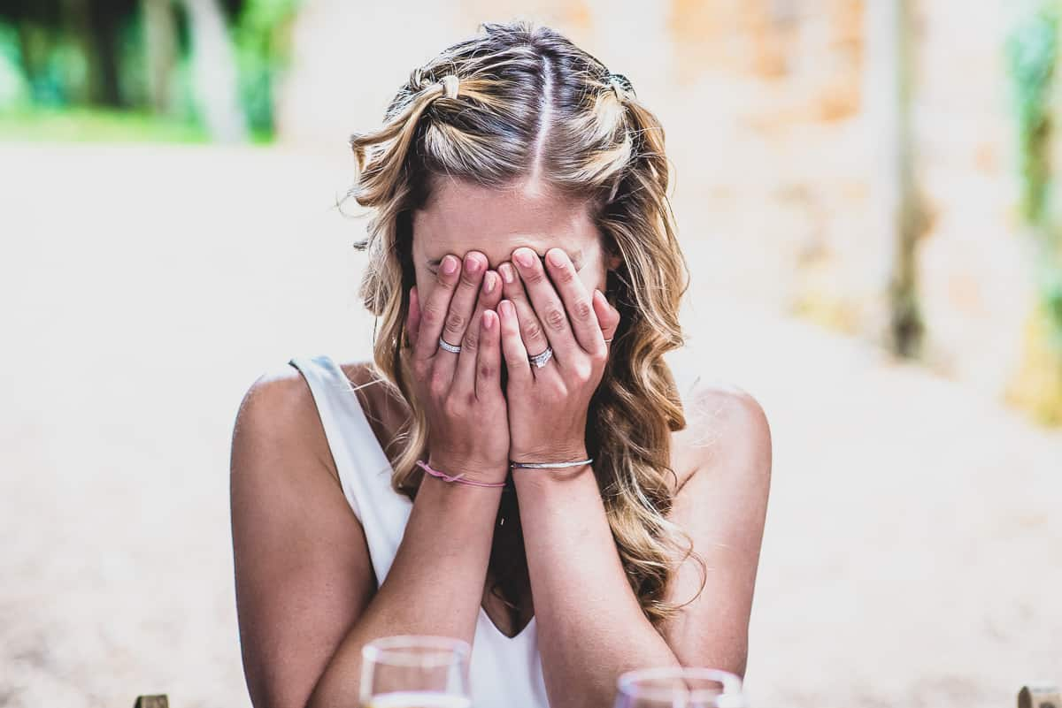 Bride puts her hands to her face in embarrassment during the speeches