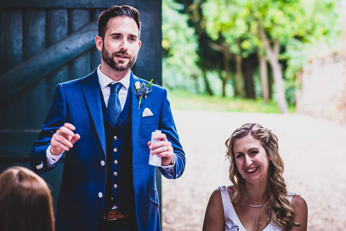 Animated groom during wedding speech with bride chuckling alongside him.