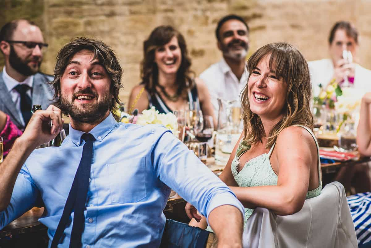 Wedding guests roaring with laughter at real fun and relaxed and informal wedding reception.