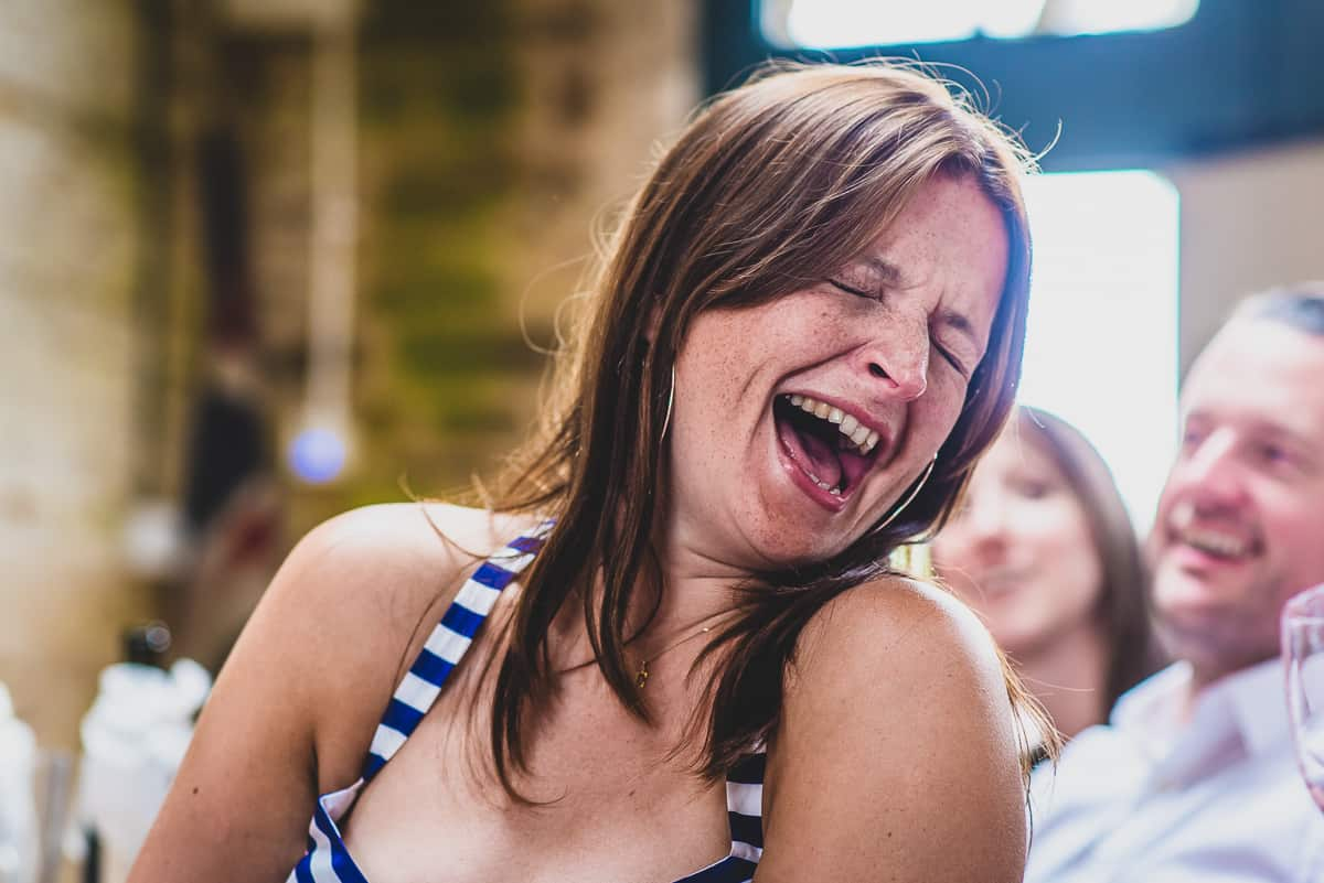 Woman throws her head back with laughter. wedding speech relaxed and informal wedding.