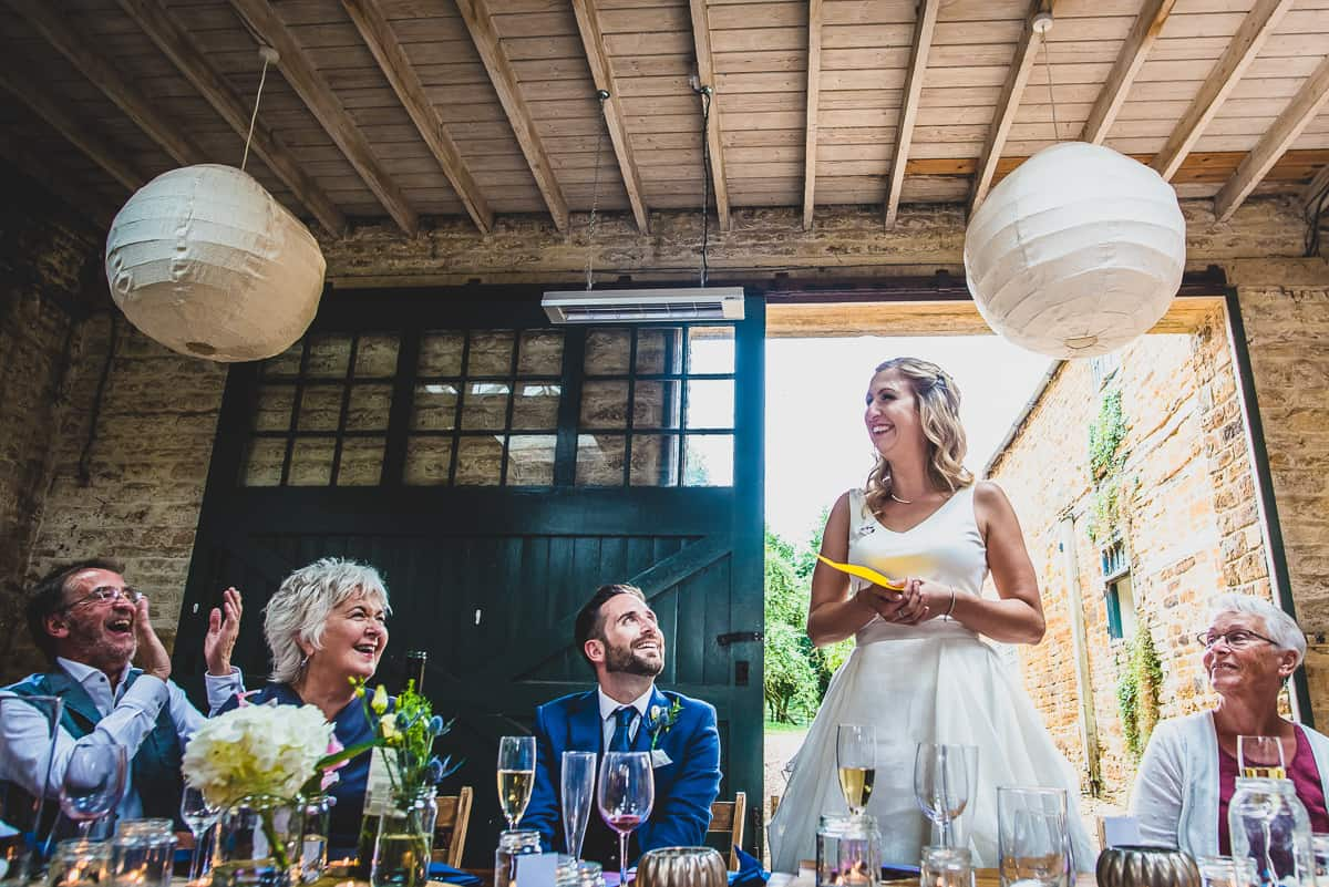 Bride enjoys her moment during her speech at super relaxed and fun wedding reception in a converted barn.