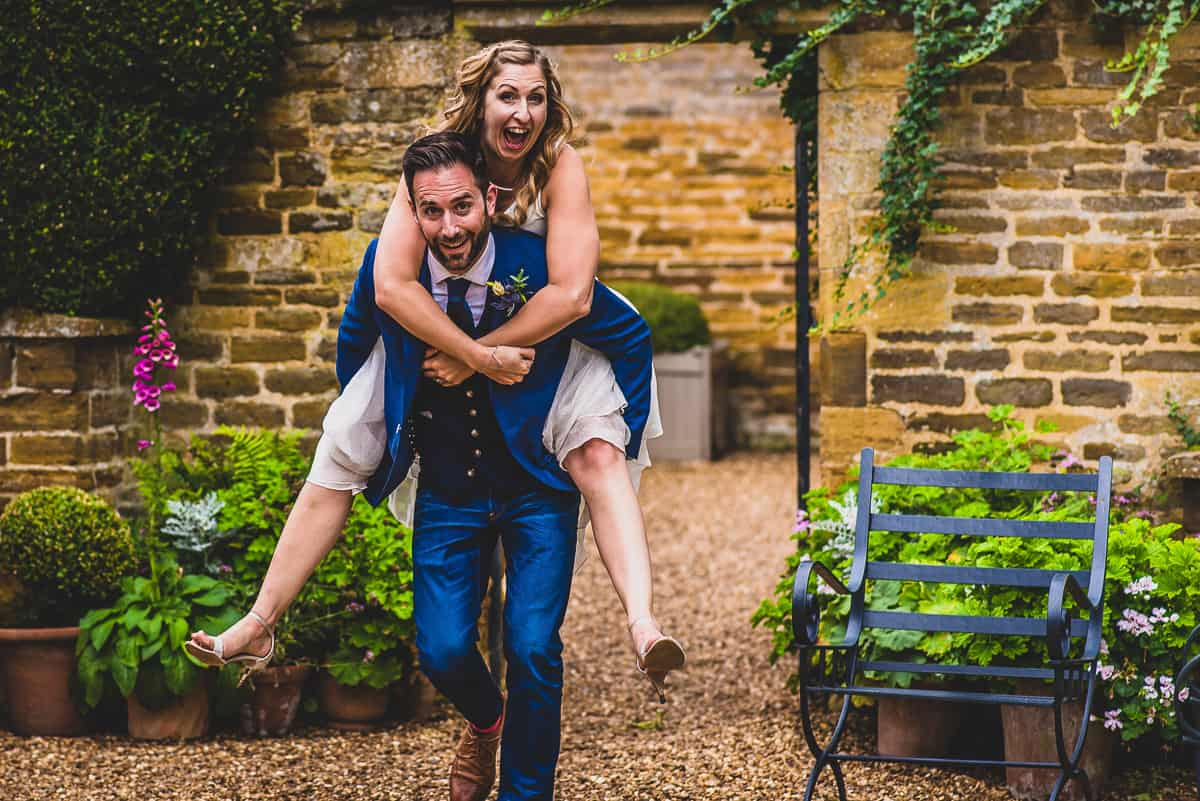 Groom carries his wife in a piggyback at relaxed wedding at Mears Ashby hall