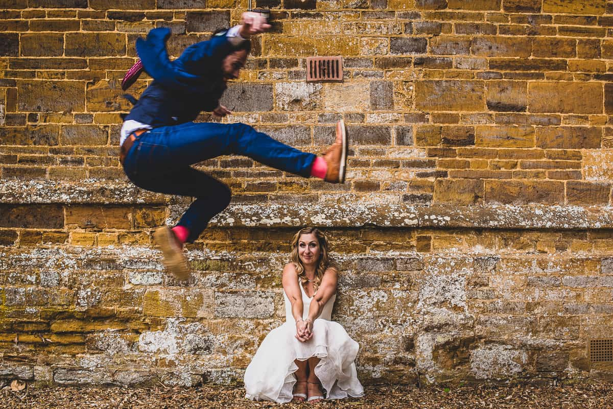 Groom leaps over his Bride fun and relaxed wedding portrait.