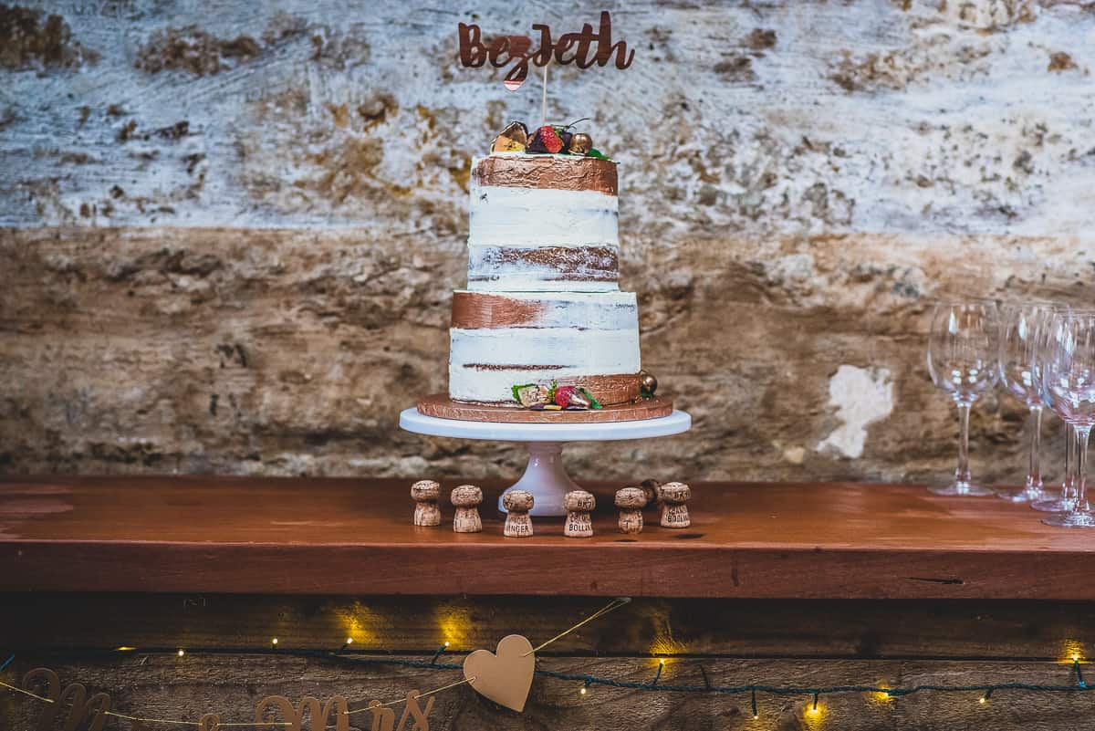 Wedding cake surrounded by Champagne corks.