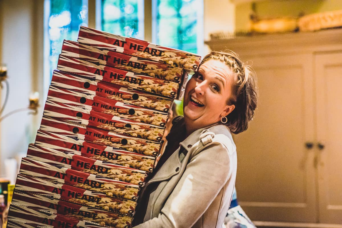 Lady carrying pizza boxes and smiling