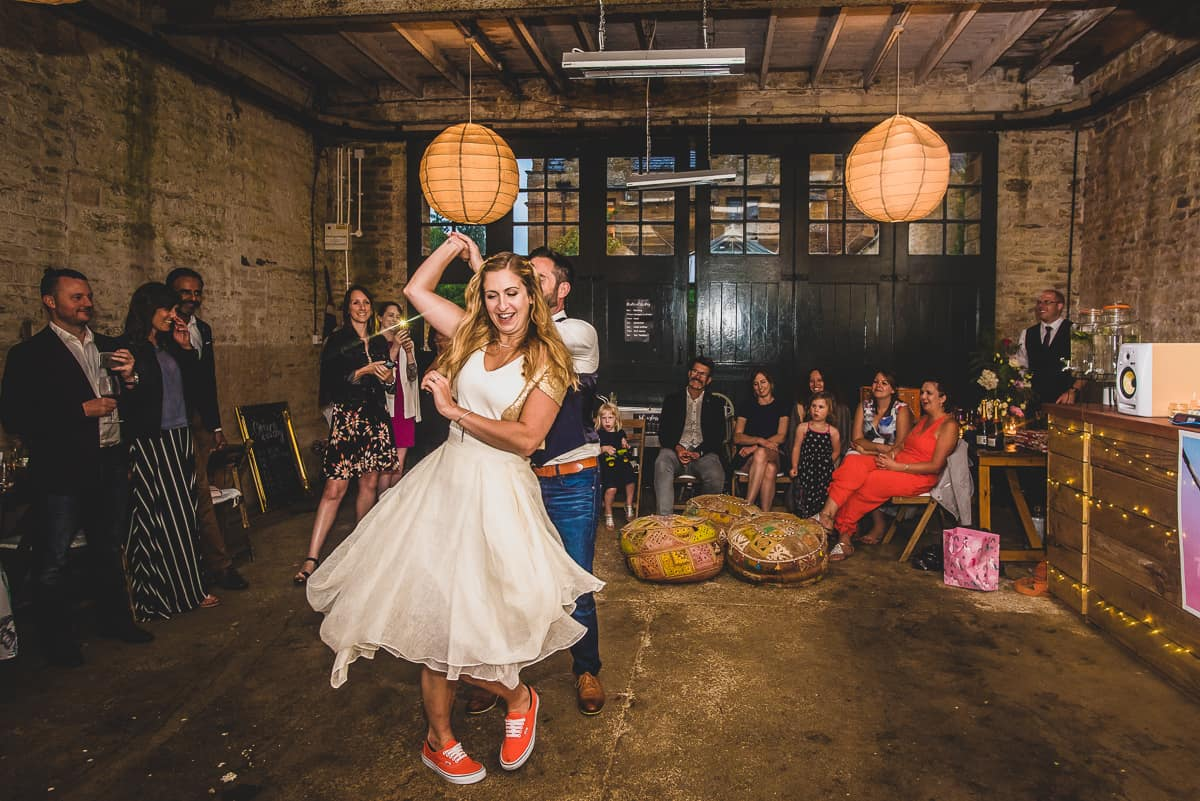 fun and informal wedding first dance in barn and bride in converse trainers.
