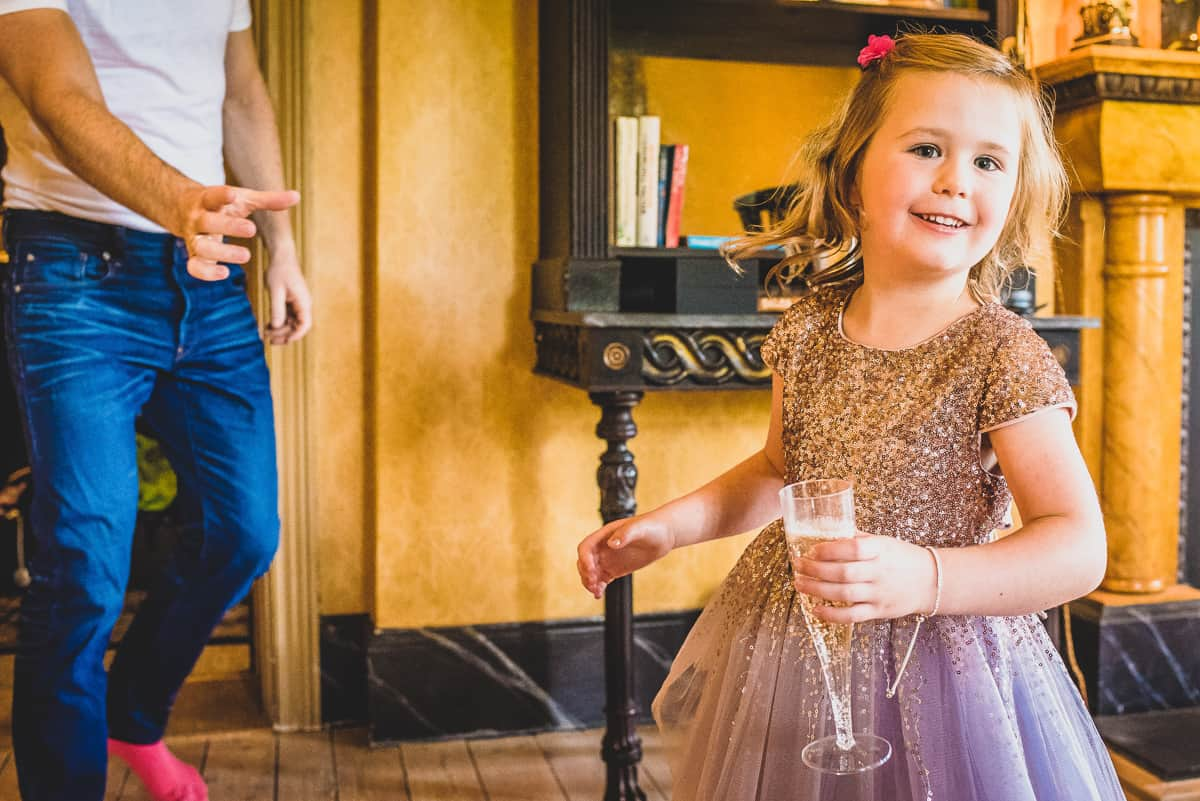 Smiling child caring a glass of fizz during bridal prep.