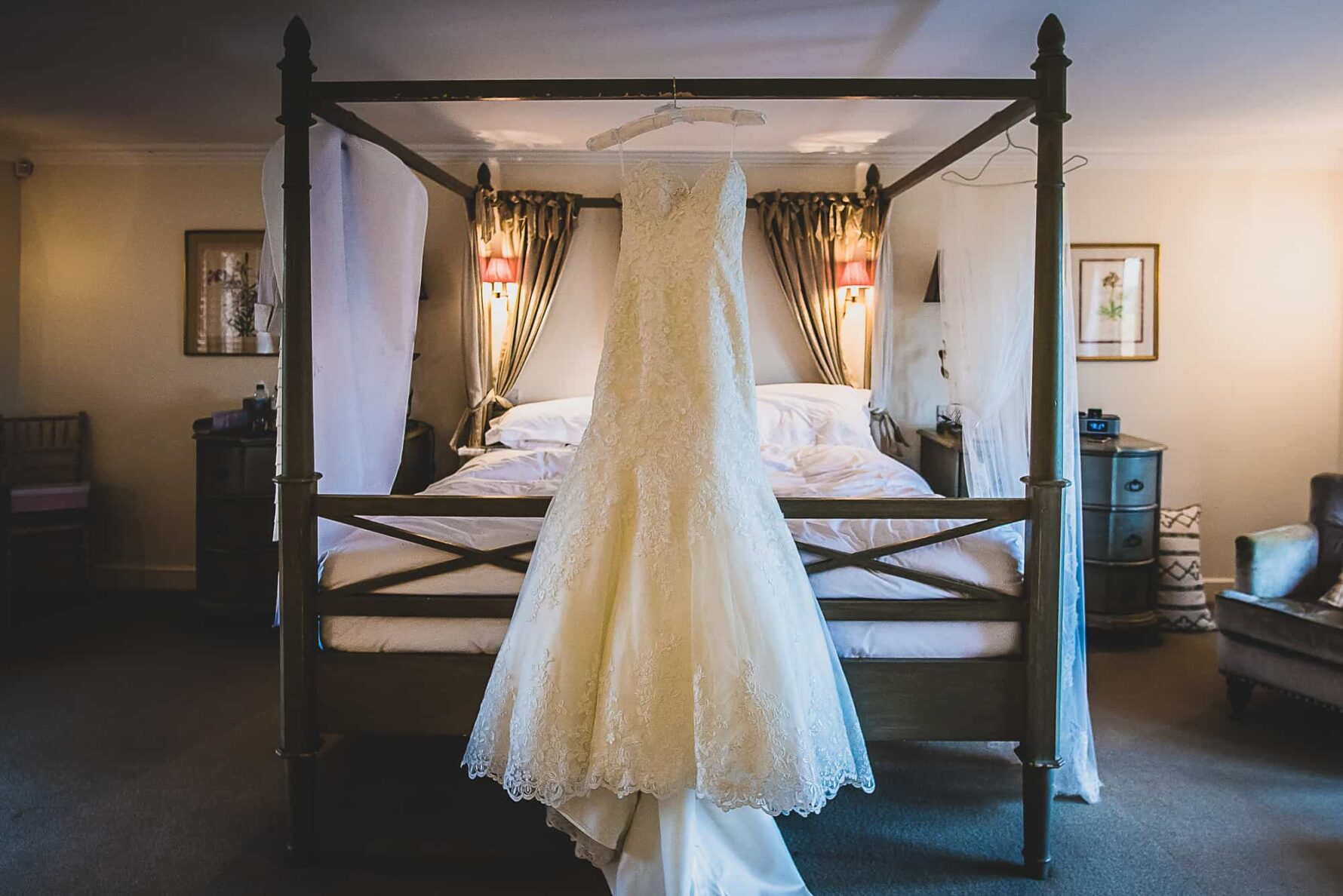 Bride's dress hangs on the bed in the bridal suite of The Old Hall in Ely