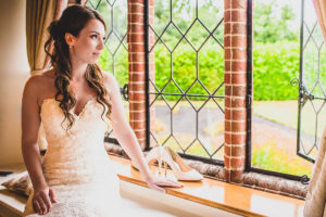 Bride sitting by the window at The Old Hall in Ely