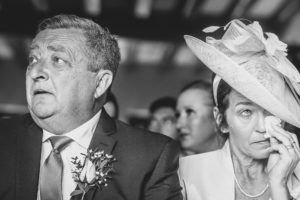 Mother of the bride wipes away a tear during wedding ceremony at The Old Hall Ely