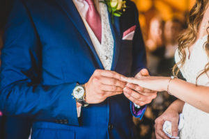 Groom placing the ring on the bride's finger. Wedding at The Old Hall in Ely.