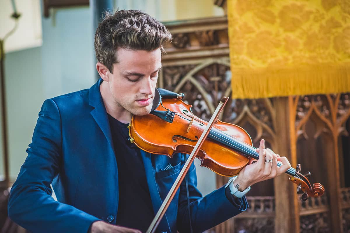 A Violin player warming up before playing at a Christening and Wedding ceremony