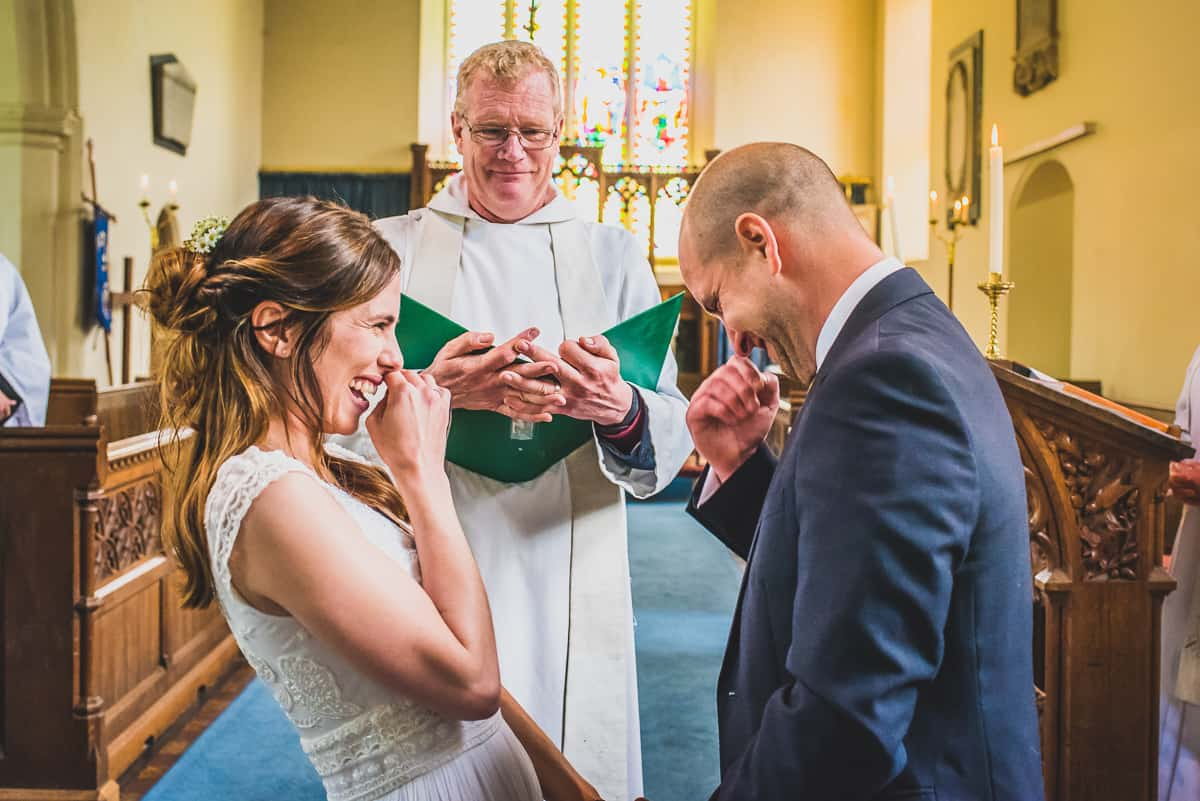 Bride and Groom giggle together as guests realise they are at a surprise wedding.
