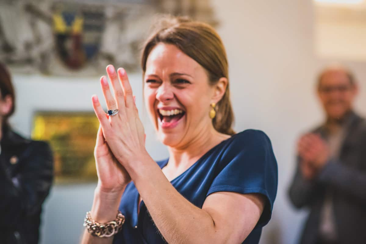 Wedding guest applauds while laughing at secret wedding ceremony.