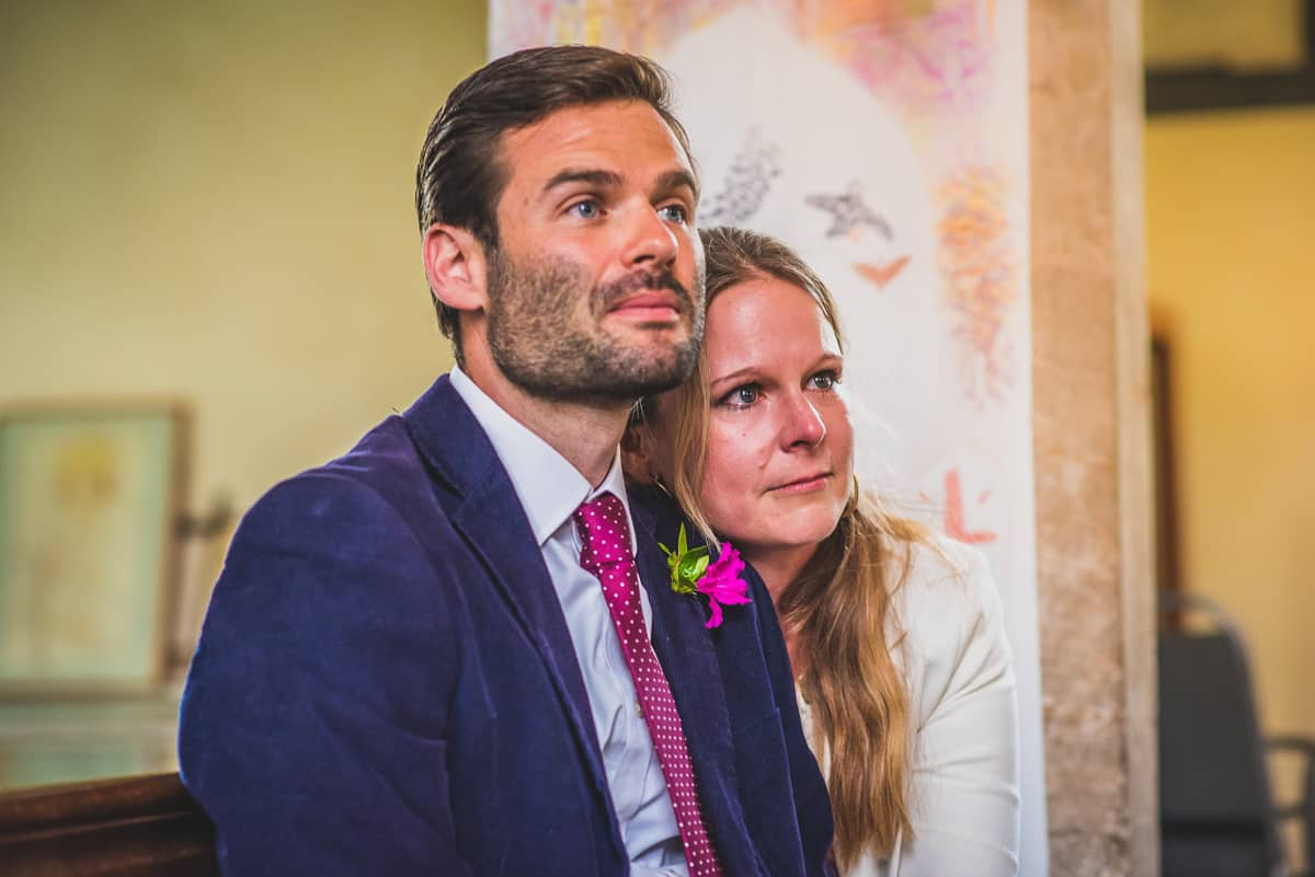 Surprise wedding guests look on with tears in their eyes.