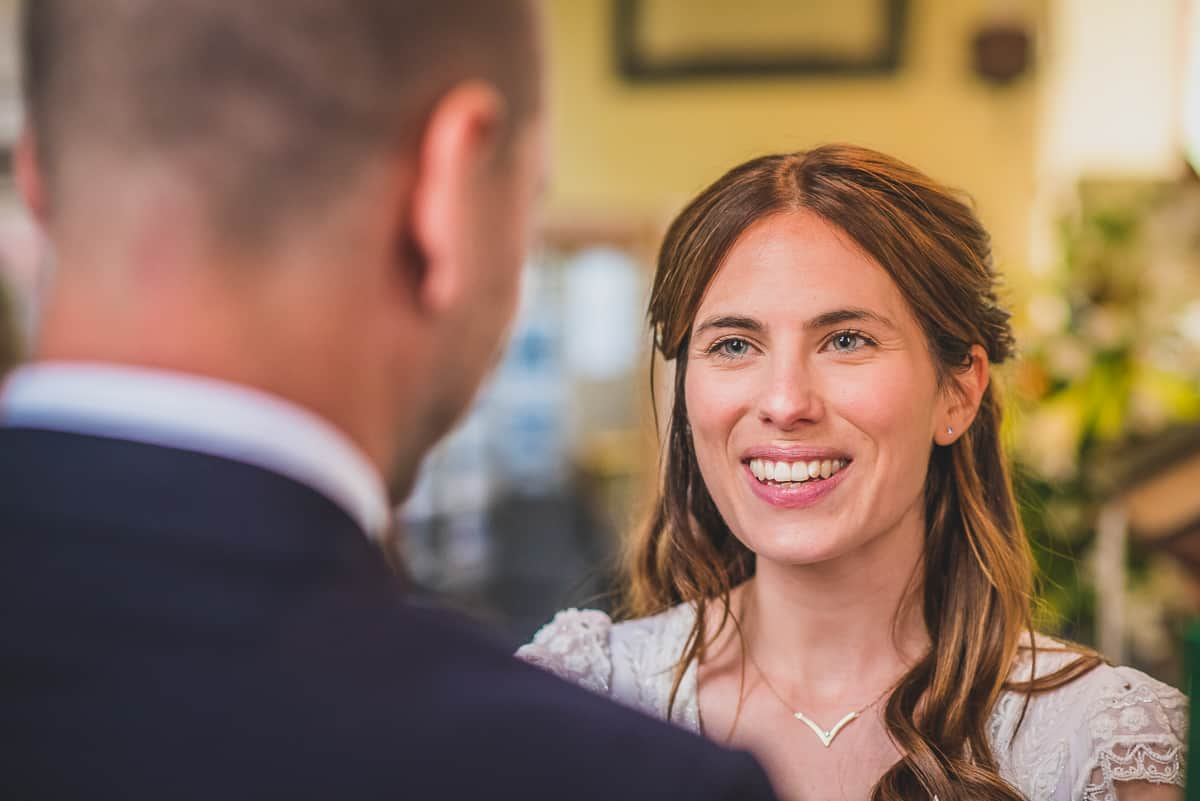 Bride smiles at groom during her Suffolk wedding ceremony