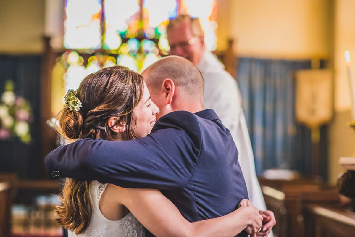 Newlyweds embrace with a hug as they are pronounced husband and wife.