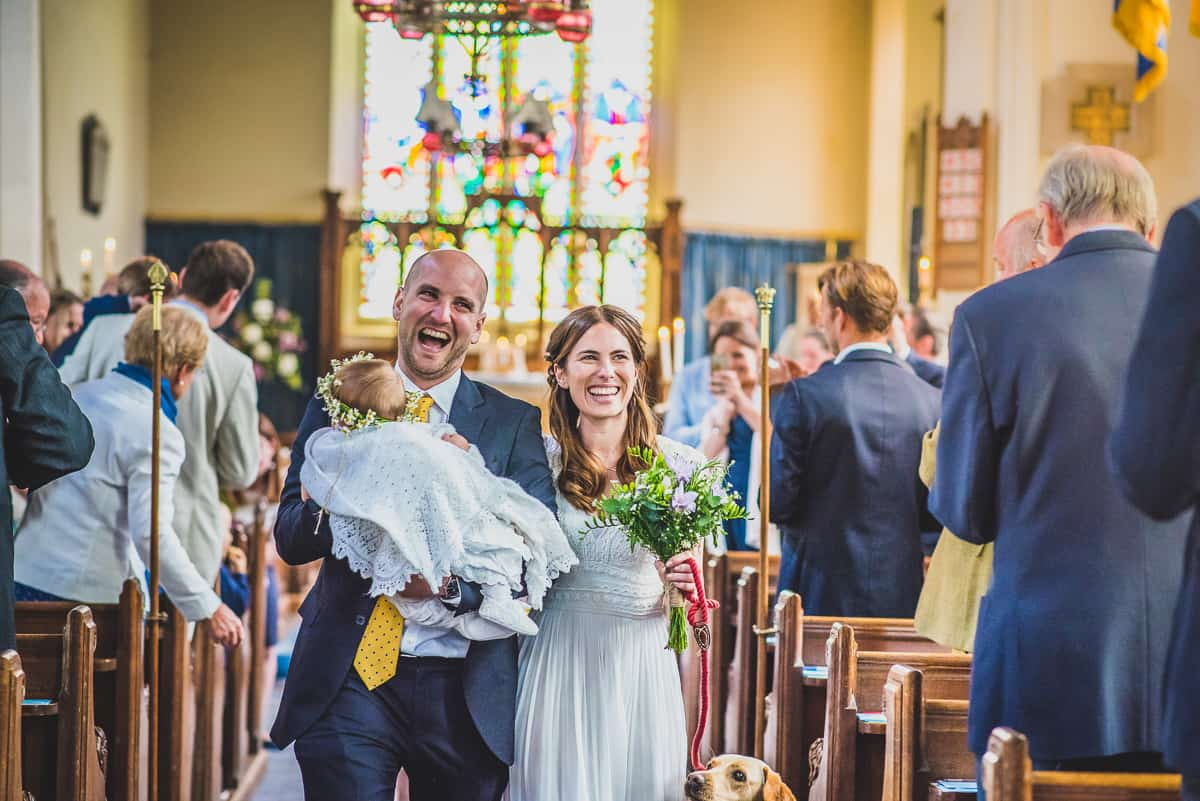 A Bride and Groom and their daughter walk the aisle after a surprise wedding ceremony in Suffolk.