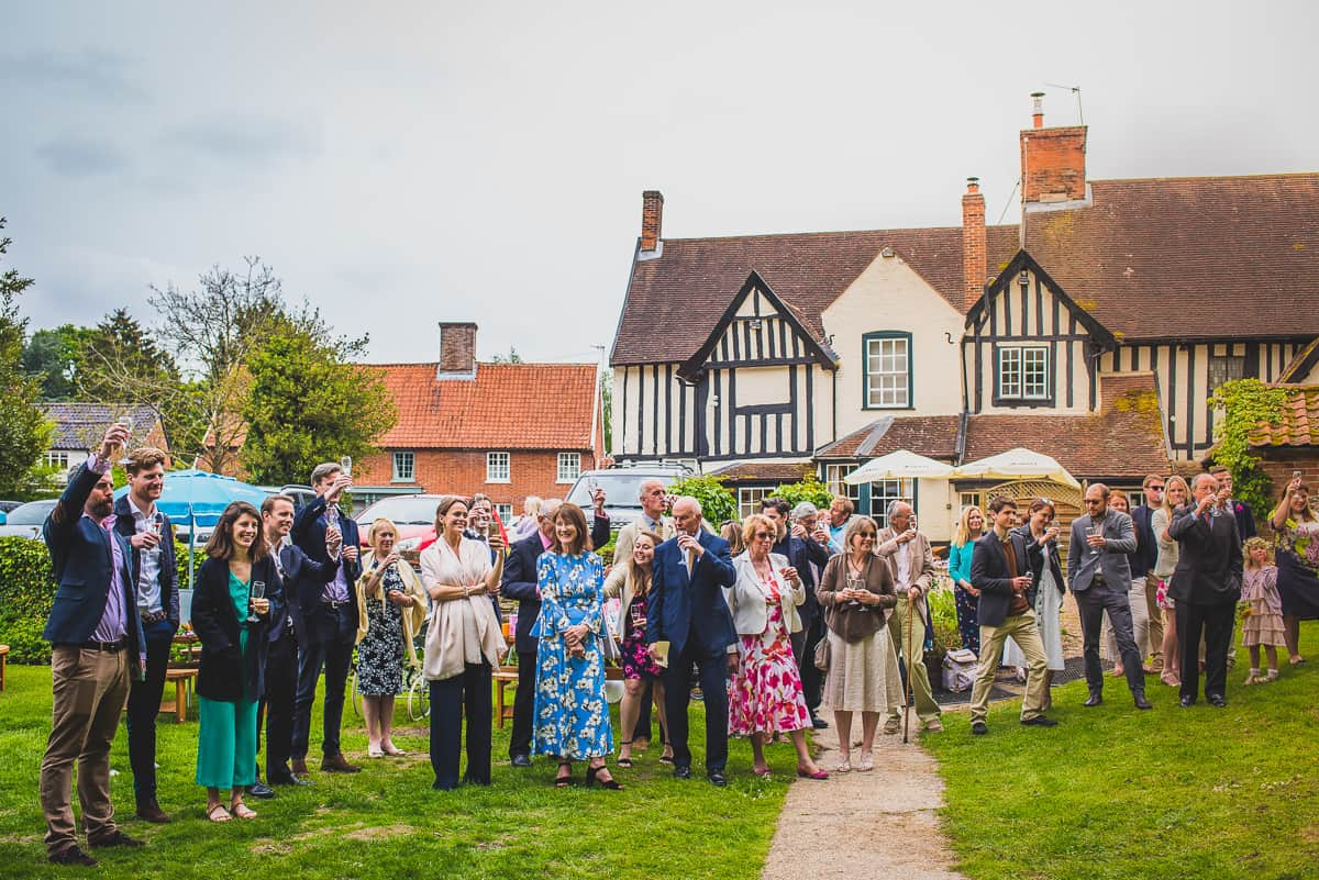 Guests at wedding at The Swan pub in Eye in Suffolk raise their glasses to the happy couple.