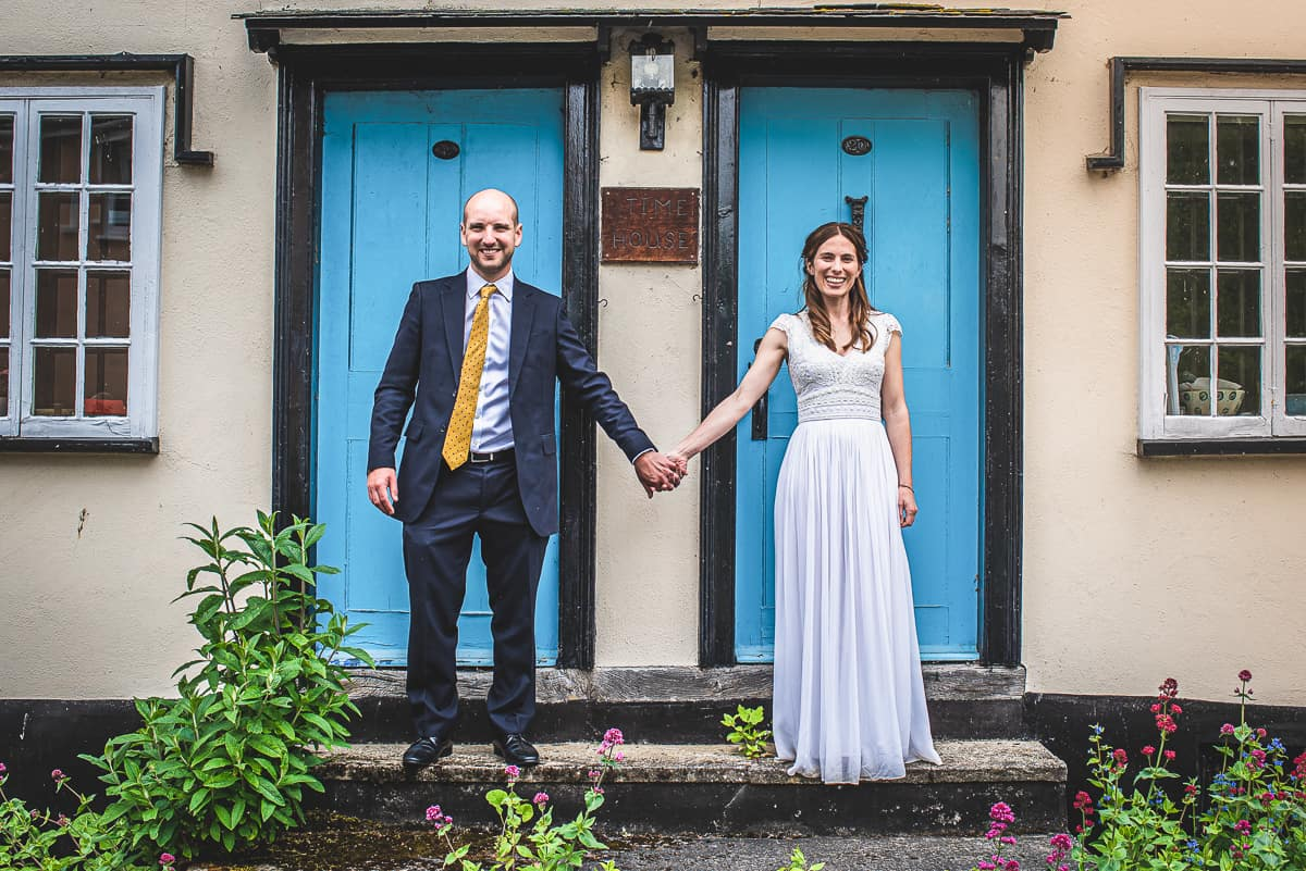 Newlyweds pose outside colourful front doors of house in Suffolk
