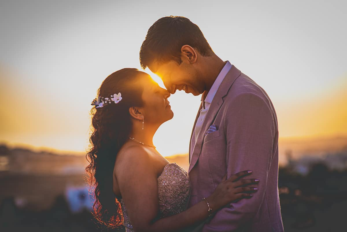 Gorgeous sunset portrait of couple at destination wedding at Diles and Rinies in Tinos Greek island.