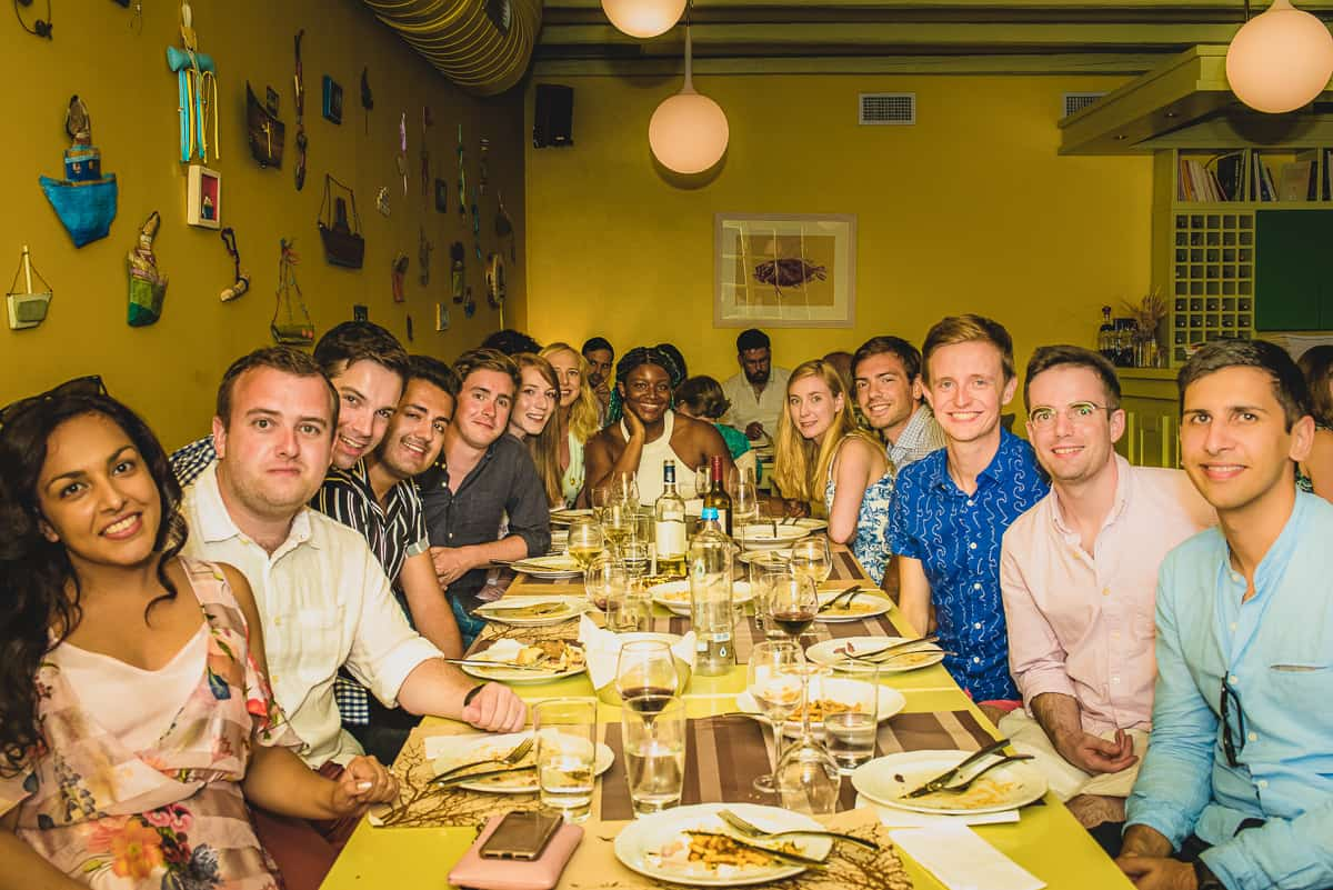 The night before the couples destination wedding guests enjoy a meal together at a local restaurant in Tinos.