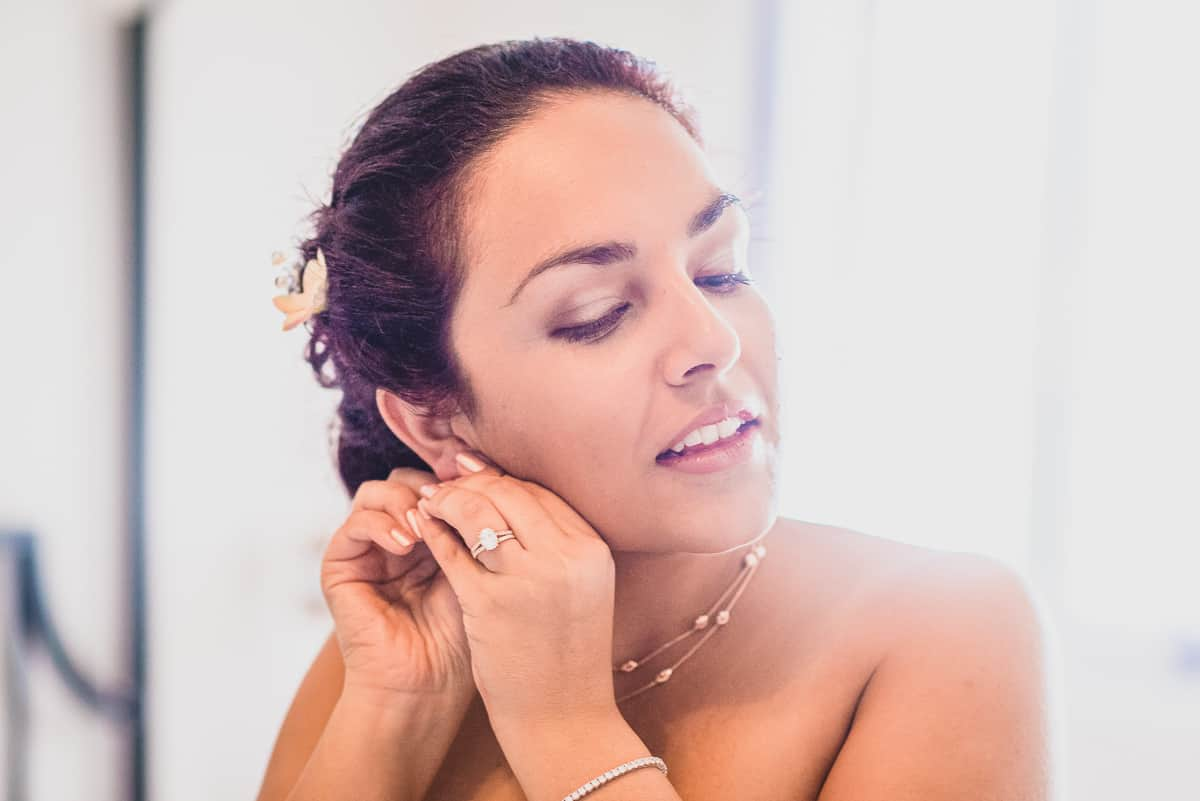 Bride puts on her earrings before the destination wedding in the Greek Island of Tinos
