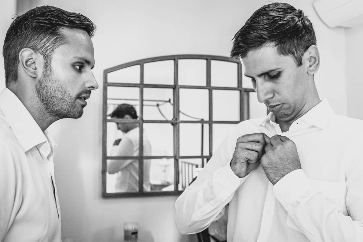 Groom adjusts his buttons in preparation for his Greek Island wedding in the sun.