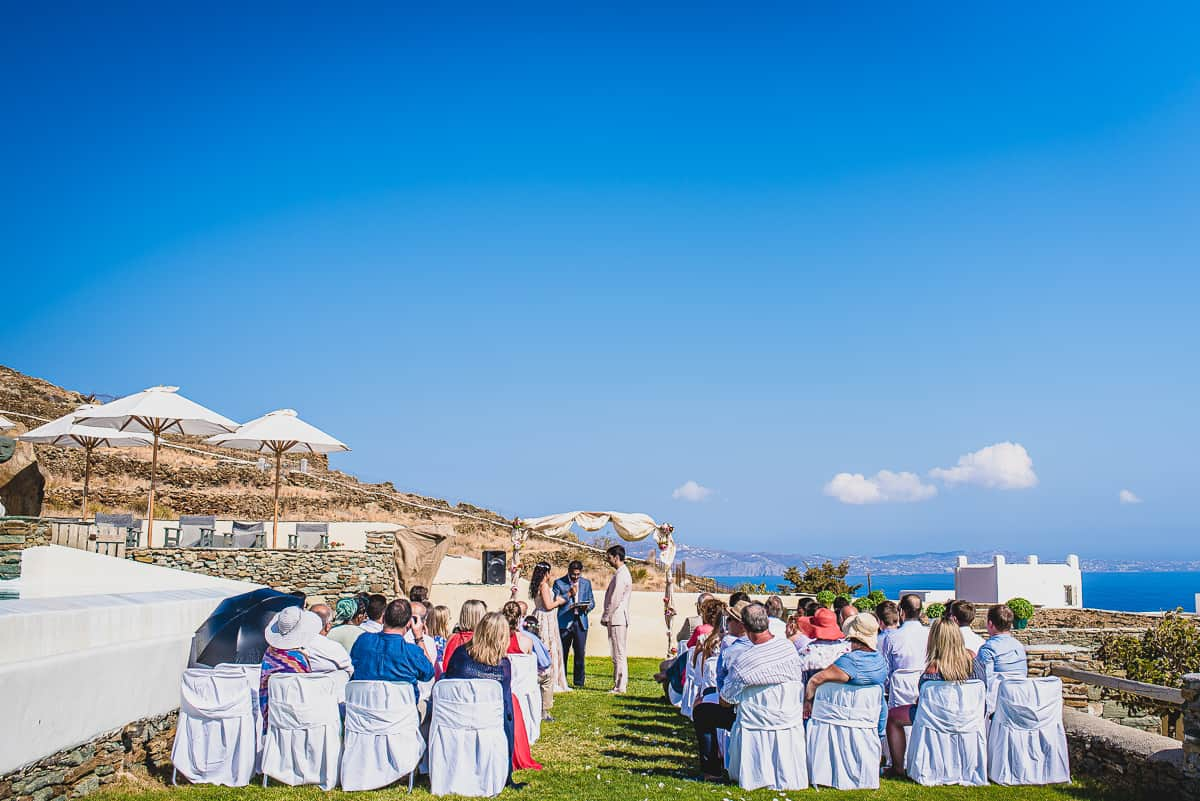 A view from the back of the small destination wedding ceremony in the Greek Island of Tino with views over the see beyond.