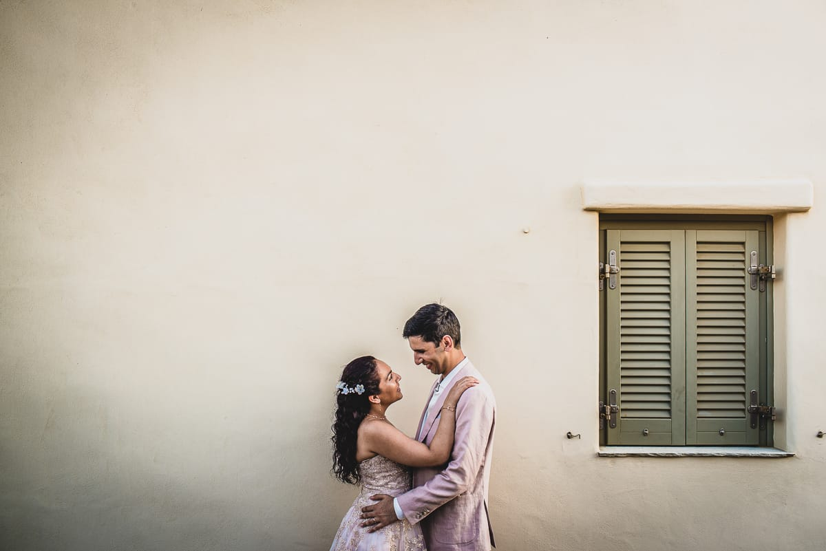 Bride and Groom portrait by the stone wall the luxury villas at Diles and Rinies in Tinos.