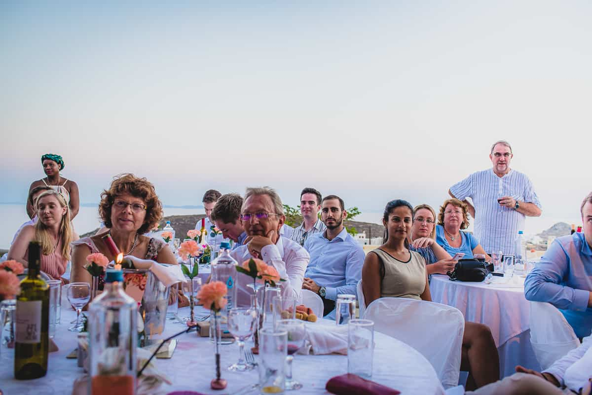 Guests enjoy open air wedding speeches at Diles and Rinies with the sea behind.