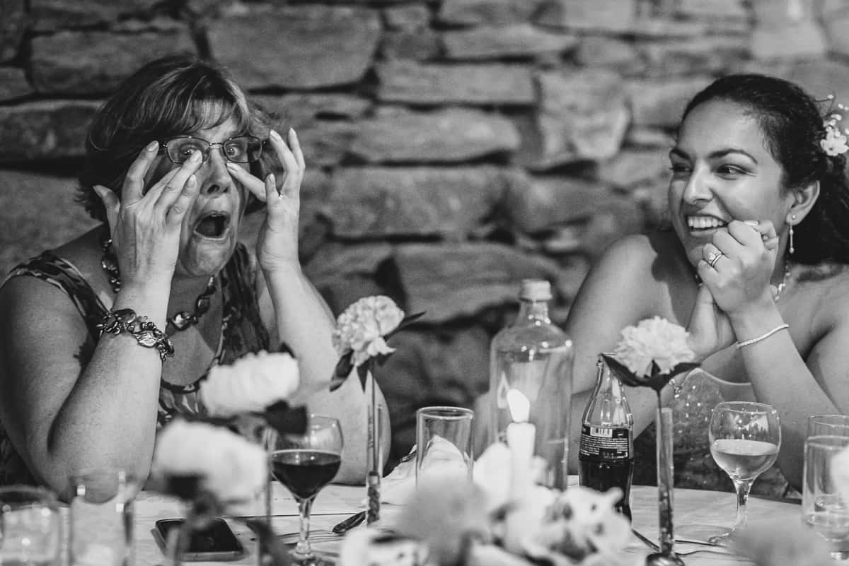Groom's mother wipes away tears of laughter during the wedding speeches.