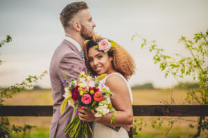 Beautiful bride and her groom in the fields of Willow Grange Farm wedding venue near Cambridge