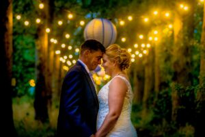Newlywed couple in the wooded avenue at Horsley Hale Farm in Cambridgeshire