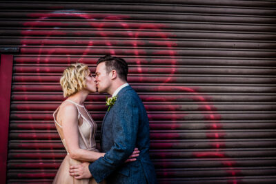Bride and groom kissing with graffiti behind at London Wedding