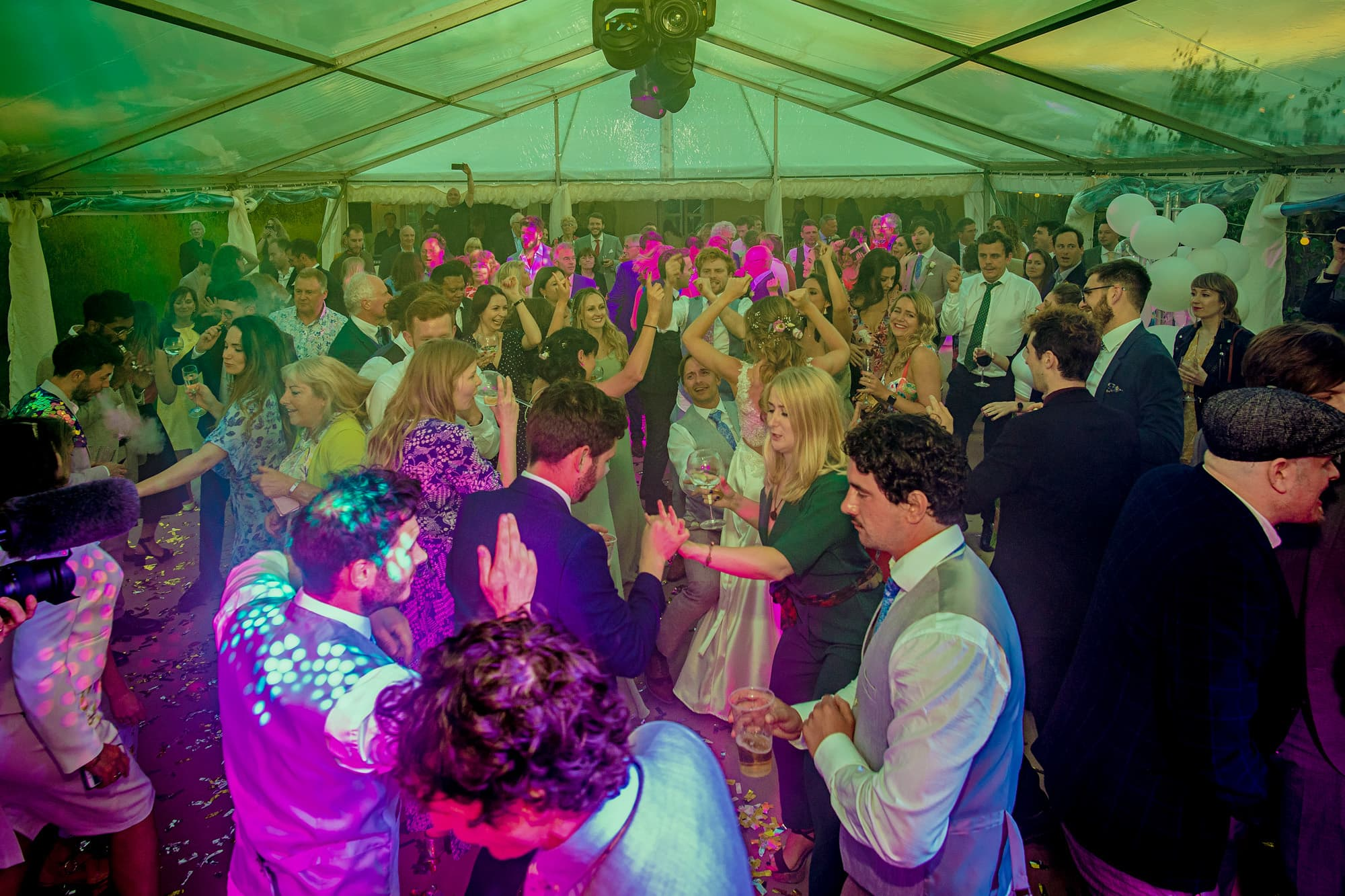 Guests dance to a live band at a wedding in Cambridgeshire